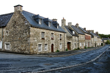 built in: Quiet street with quaint old granite stone houses built in traditional Breton architectural style in a small town in Brittany France  Stock Photo