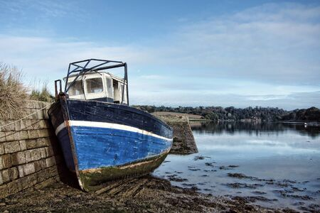 junked: Abandoned wood fishing boat tied to an old stone masonry dock in an empty estuary river port at low tide in the scenic Brittany region of France  Stock Photo