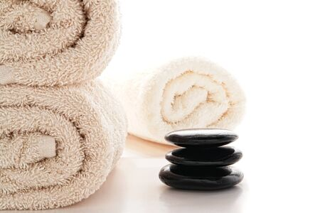 Polished black hot massage stones Zen cairn with soft and fluffy rolled cotton bath towels over white in a spa  Stock Photo