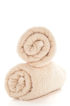 Soft and fluffy beige color cotton bath towels rolled and stacked over white