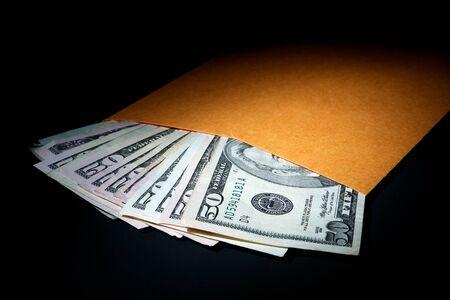 payout: Pila de circulaci�n billetes de alta denominaci�n d�lar de los EE.UU. que salen de una llanura sobre de manila marr�n como una met�fora de los sobornos en efectivo bajo la mesa y la corrupci�n ilegal dinero por su silencio a la luz dram�tica sobre negro