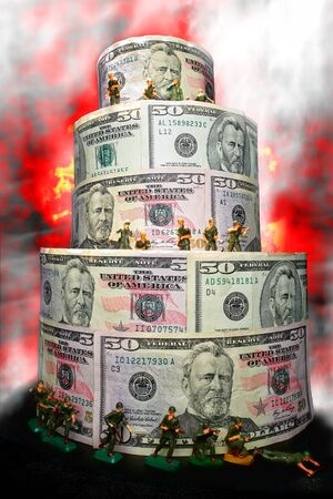 risk of war: Miniature toy soldiers at war surrounded by smoke and fire defending a metaphoric economic financial fortress made of US dollar bills as a metaphor for the defense of the American economy against monetary assault and currency attack  Stock Photo