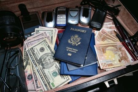 Criminele spion contra-missie kit in een top-geheime regering inlichtingendienst koffer met nep diverse nationaliteit paspoorten en internationale munt geld plus wegwerp mobiele telefoons en undercover spionage gadgets