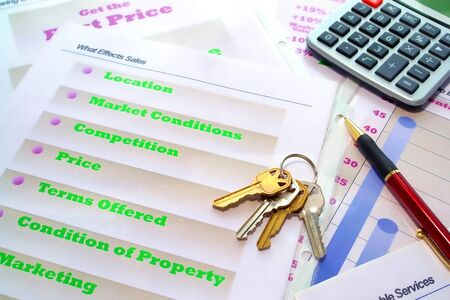 licensed: Set of house keys and calculator on real estate agent marketing plan binder with loose demonstration pages during a listing presentation (material created and designed by author a former Realtor and licensed broker)