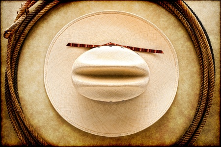 American West rodeo cowboy white hat and authentic vintage Western lariat style lasso hondo loop on smooth brown leather texture background photo