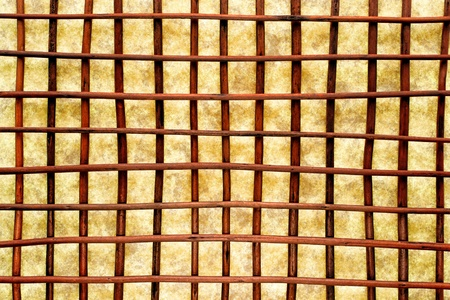 crisscross: Asian inspired Eastern decor style background with decorative brown wood reeds in a crisscross grid lattice