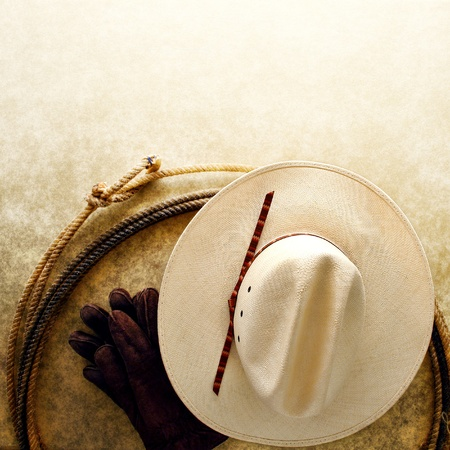 hondo: American West rodeo cowboy white hat and authentic Western lariat style lasso with hondo loop on smooth grunge leather texture background