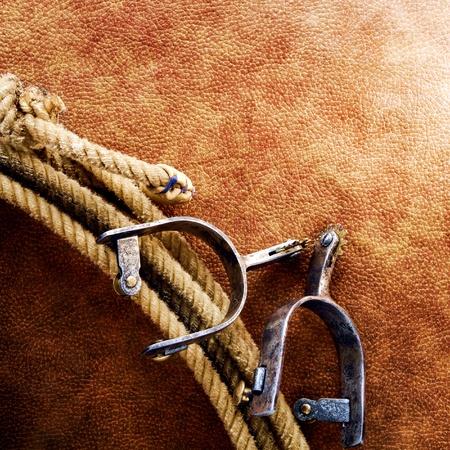 ranching: American West Rodeo Cowboy lazo lazo con el corte y la cuerda espuelas en fondo del grunge viejo de cuero marr�n Foto de archivo