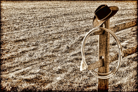 west end: American West rodeo cowboy hat and authentic lariat lasso on a fence end post in a ranch  field in vintage grunge nostalgic sepia Stock Photo