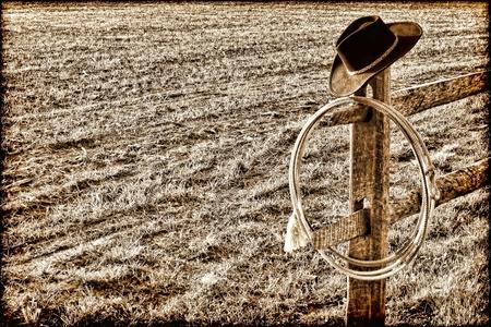 rodeo americano: American West rodeo sombrero de vaquero y lazo lazo aut�ntico en un mensaje final en un campo cerca de rancho en el grunge, cosecha, nost�lgico sepia Foto de archivo