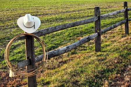 ranch: American West rodeo vintage cowboy hat and authentic lariat lasso hanging on a ranch fence post near a prairie field Stock Photo
