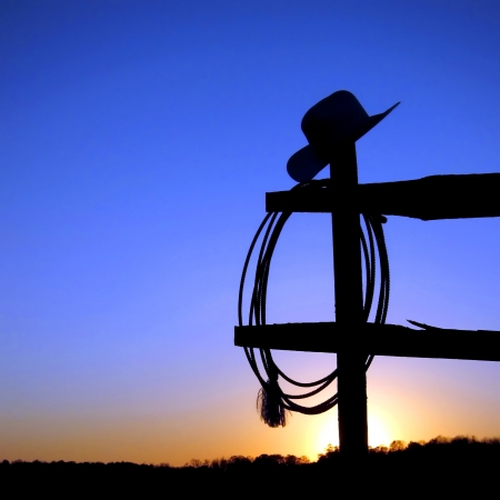 American West rodeo authentic cowboy hat and lariat lasso hanging on a ranch fence post in backlit silhouette over blue sky at sunset