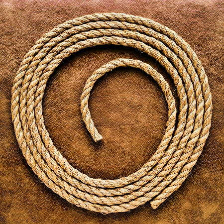 coiled rope: American West rodeo natural hemp fiber rancher rope for ranching and steer roping on grunge leather brown surface