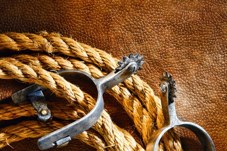 spurs: American West rodeo cowboy ranching rope with western riding spurs on old brown leather grunge background