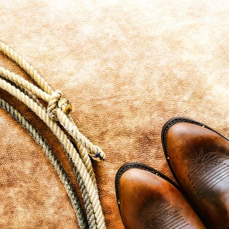 American West rodeo cowboy traditional leather boots and authentic Western lasso lariat or loop on grunge leather texture background photo