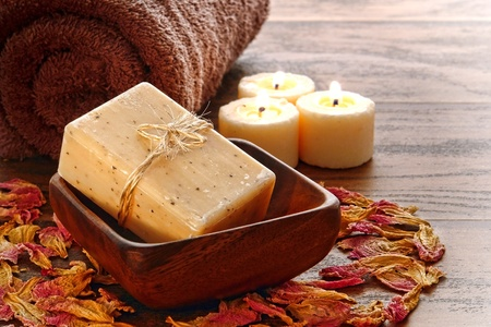 craftsperson: Natural artisan made Marseilles type aromatherapy and body care bath soap bar in a wood dish with towel and burning candles for a pampering cleansing session in a relaxation spa