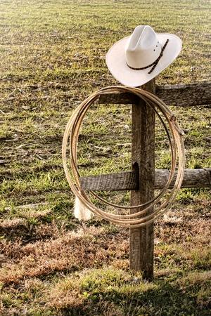 ranching: American West rodeo sombrero de vaquero y lazo lazo aut�ntico colgado en un poste cerca de rancho de final Foto de archivo