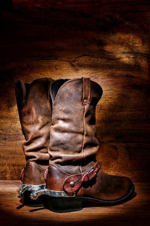 spurs: American West rodeo cowboy traditional leather boots with authentic Western riding spurs over vintage wood in a ranching barn Stock Photo