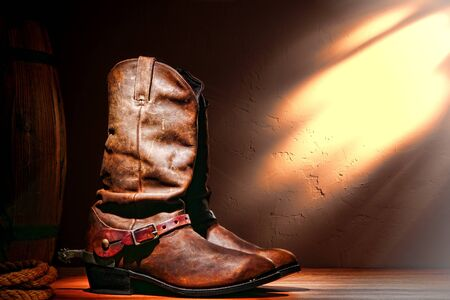 spurs: American West rodeo cowboy traditional leather working roper boots with authentic Western riding spurs in a vintage ranch barn