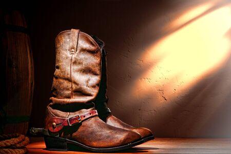 american rodeo: West americano rodeo in pelle di lavorazione tradizionali stivali da cowboy Roper con autentici speroni a cavallo occidentale, in un fienile ranch d'epoca Archivio Fotografico