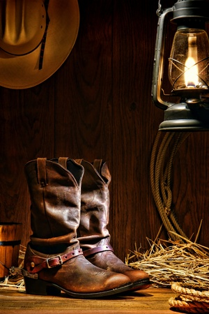 spurs: American West rodeo cowboy traditional leather working roper boots with authentic Western riding spurs in a vintage ranch barn with ranching tools lit by an old nostalgic kerosene oil lantern