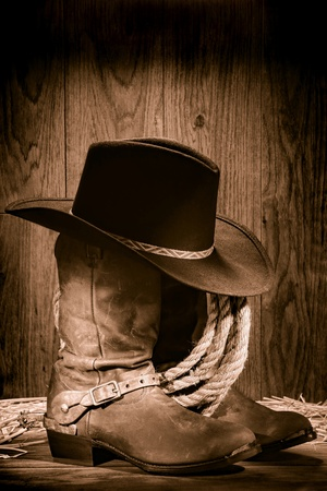 American West rodeo cowboy black felt hat atop worn western boots and spurs with old ranching rope in an antique wood barn in nostalgic vintage sepia photo