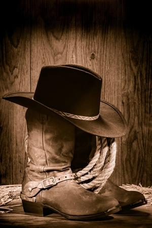 rodeo americano: American West rodeo vaquero sombrero de fieltro negro encima de las botas occidentales gastados y estimula con la cuerda de la ganadería de edad en un granero de madera antigua en sepia nostálgico vendimia