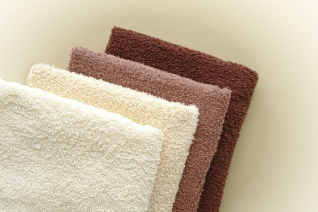Soft and fluffy cotton hotel quality bath towels in light beige to dark brown fashion colors in a stack over soft leather surface