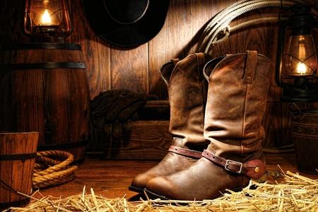 american rodeo: American West Rodeo cowboy de cuero de trabajo tradicionales botas de ranchero roper con auténticos estribaciones occidentales que viajaban en un granero rancho de la vendimia con las herramientas de la ganadería iluminado por lámparas viejas nostálgicas de queroseno del petróleo Foto de archivo