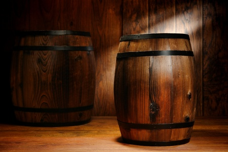 Old fashioned antique whisky wood barrel and wine keg container in a nostalgic American antique brown wooden warehouse decor Stock Photo
