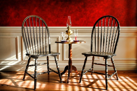 faux: Antique black distressed Windsor style chairs and mahogany table with glasses and oil lamp in an early American Empire colonial decor historic home interior parlor with decorative wall molding and faux finish red paint treatment