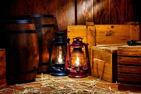 candil: Pasado de moda la luz de linterna de queroseno lámparas de estilo petrolero en llamas en un almacén de envío de antigüedades de época con contenedores y cajas de madera antiguas cajas de almacenamiento de madera cerca de retro barriles de whisky de transporte