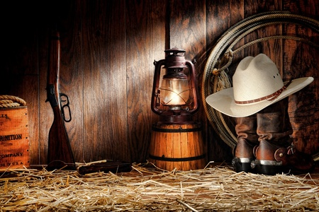 American West rodeo cowboy authentic working gear with white straw hat atop genuine roper leather boots and old Western rifle gun in a vintage ranch wood barn with various ranching tools lit by an old nostalgic kerosene oil lantern lamp Stock Photo