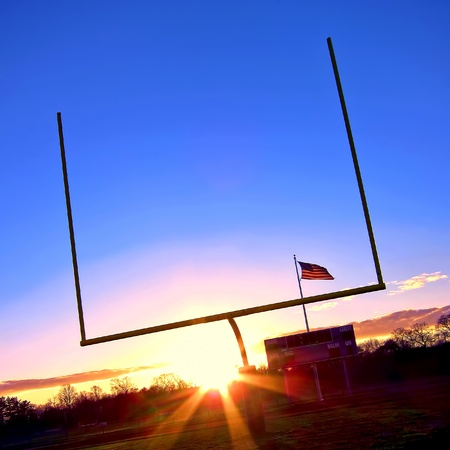 scoreboard: American football goal posts at end zone with stadium score board and US flag post at sunset over blue sky