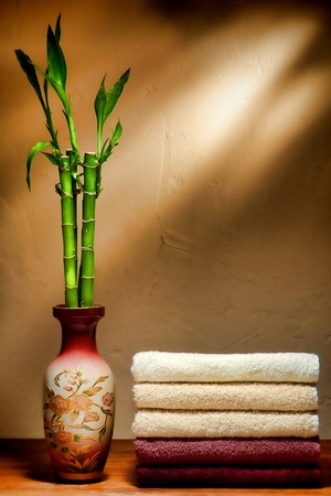 neatly: Stack of neatly folded soft and fluffy assorted colors cotton towels in elegant brown tones and bamboo stems in an Eastern style Asian vase in a relaxation and wellness spa