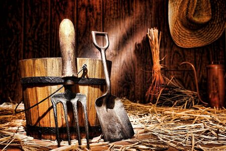 spading fork: Antique gardening tools old steel shovel and vintage spading fork resting on an aged wood bucket in an older country garden shed Stock Photo