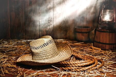 ranching: Old farmer straw hat over a sisal ranching rope on wood floor covered with loose hay lit by an antique kerosene lantern style oil lamp in an antique ranch barn with dust and smoke in diffused light  Stock Photo