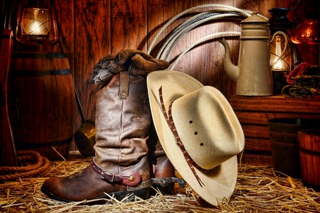 west: American West rodeo cowboy traditional white straw hat resting on leather working rancher roper boots with authentic Western riding spurs and gloves in a vintage ranch barn with antique ranching supplies lit by old nostalgic kerosene lantern oil lamps