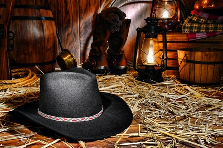 American West rodeo cowboy traditional black felt hat on straw covered wood floor in a vintage ranch barn with antique ranching supplies and rancher tools lit by old nostalgic kerosene lantern oil lamps