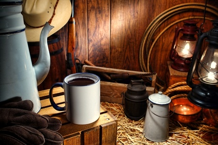 Old American West enamel coffee mug and vintage pot with traditional working cowboy tools and ranching supplies in an antique Western ranch chuck wagon  Stock Photo