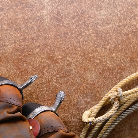 American West rodeo cowboy traditional leather boots with riding spurs and authentic Western lasso lariat with hondo or honda loop on brown leather texture background photo