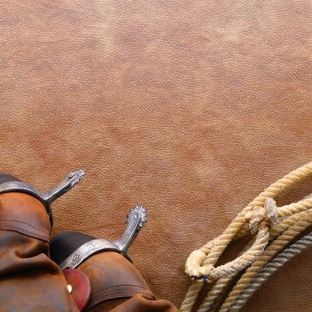 american rodeo: West americano rodeo stivali di cuoio da cowboy a cavallo con gli speroni tradizionale e autentico occidentale lazo lariat con hondo o honda anello su sfondo texture in pelle marrone