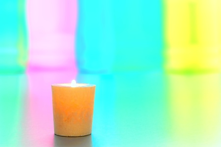 votive candle: Decorative votive candle burning with a soft glow flame over subdued pastel colors background Stock Photo