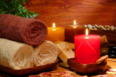 Festive aromatherapy pillar candles burning with a soft glowing flame and cotton bath towels for a soothing relaxation and pampering treatment holiday gift session in a wellness spa