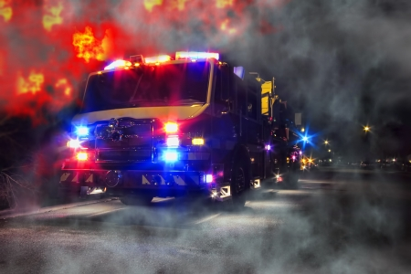flashing: Emergency firefighter rescue truck with flashing lights at disaster night scene of an inferno blaze fire with intense burning flames and heavy smoke Stock Photo