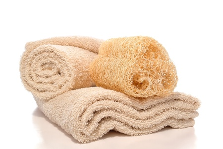 Natural loofah skin cleansing care and exfoliating scrub sponge on soft cotton beige bath towels over white