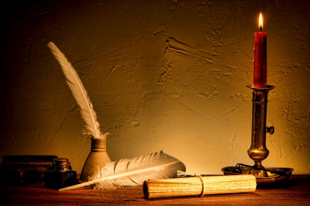 candlelight: Antique parchment paper sheets roll tied with string lit by candlelight on a vintage colonial wood desk with ink writing feather quill and old candle light burning in an ancient historic candleholder in retro olde master painting style  Stock Photo