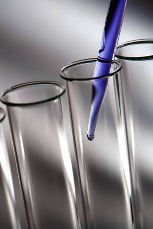 Laboratory pipette with drop of blue liquid over empty glass test tubes for a scientific experiment in a science research lab photo