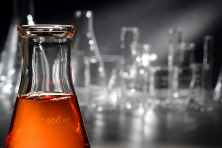 Scientific laboratory glass conical Erlenmeyer flask filled with amber orange chemical liquid for a chemistry experiment in a science research lab