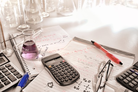 Portable pocket electronic scientific calculator and laboratory conical Erlenmeyer flask filled with purple chemical liquid on notepads with hand written chemistry assay formulas and scientist notes for an applied chemistry experiment in a science researc Stock fotó
